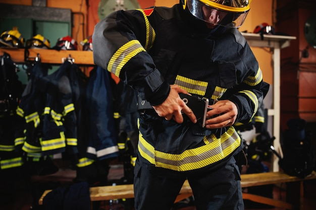 Fireman putting on protective uniform and preparing for action while standing in fire station.