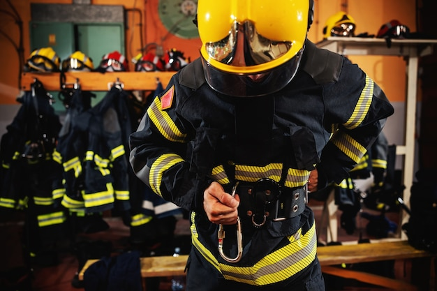Fireman putting on protective uniform and preparing for action while standing in fire station