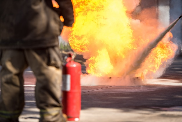 Fireman showing use a fire extinguisher on a training fire hydrant with white smoke. occupational health and safety concept.