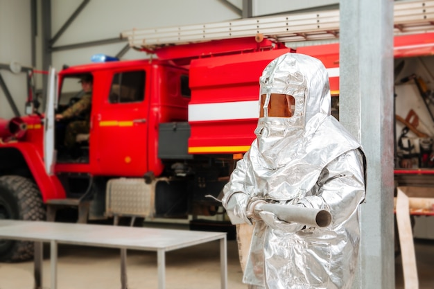 Fireman in a special foil protective suit with a fire truck on the background