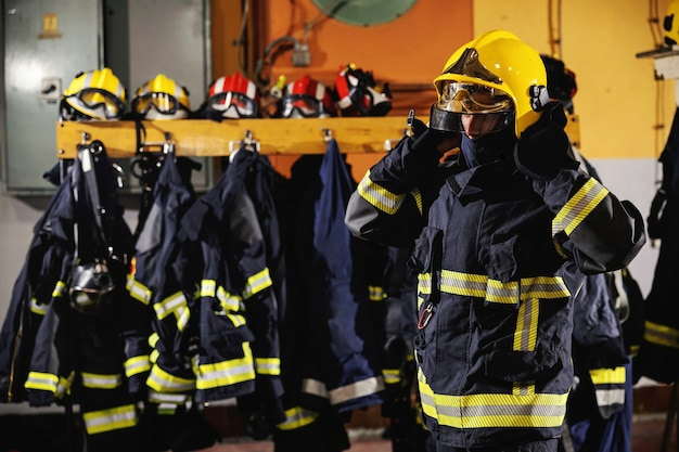 Fireman standing in fire station, putting helmet and preparing for action.