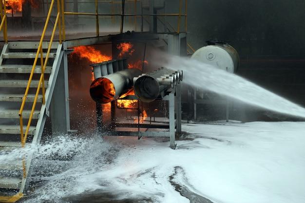 消防士の訓練スプレー水カーテンが火を止めるのを助けました。