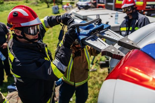 墜落した車のそばに立って、それをひっくり返そうとしている消防士。