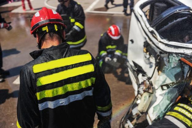 墜落した車から人を解放しようとしている消防士。交通事故で墜落した車があります。