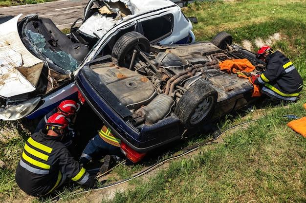 墜落した車から人を解放しようとしている消防士。