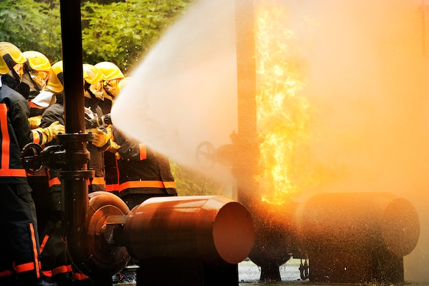 Firemen using extinguisher and water for fighter fire during firefight training.