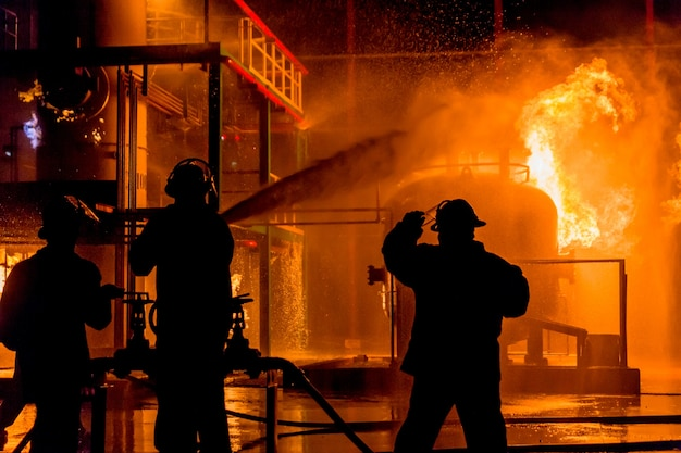 Firemen using water from hose for fire fighting at firefight training of insurance group