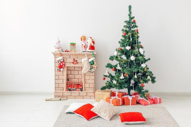 Камин и украшенная елка с подарками в гостиной