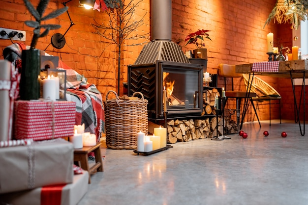 Fireplace area of a beautiful loft-style interior with real brick and concrete floors decorated for the new year holidays. the concept of home comfort