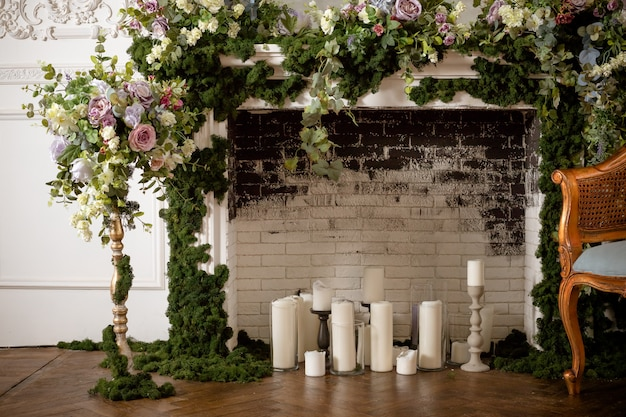 Fireplace  and candles. wedding decorated area. vintage  fireplace decorated with spring flowers, wreath, candles.brick wall.