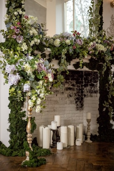 Fireplace decorated with flowers and candles. wedding decorated area. romantic place decorated with spring flowers, wreath, candles.brick wall.floral decoration