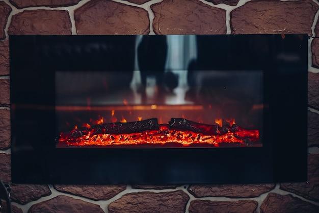 불타는 통나무가있는 벽난로. 불에 굽기 또는 연기 로그와 돌 벽난로의 클로즈업.