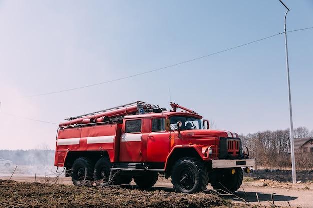 Пожарные машины припаркованы в открытом поле в сельской местности в солнечный день