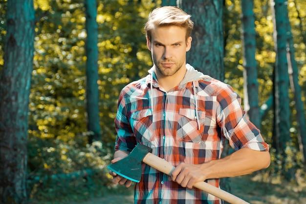 再生可能エネルギー源としての薪。斧を持っているハンサムな木こりの木こりの格子縞のシャツ