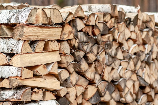 Firewood background of chopped wood for kindling and heating the house close-up. a woodpile with stacked firewood. the texture of the birch tree. banner
