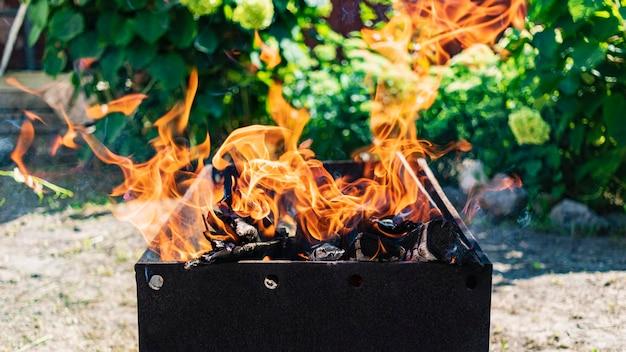 Дрова горят в мангале. отдых на природе. горячие угли. костер огонь.