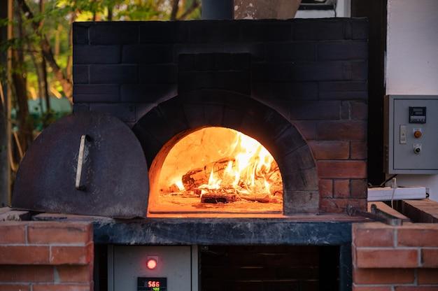 Сжигание дров в традиционной печи для пиццы в пиццерии