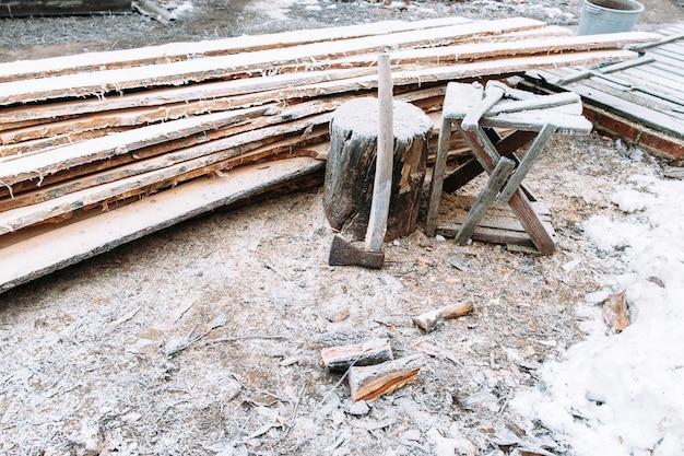 Рабочее место рубки дров залито снегом. на лесопилку пришла зима. оставленные на улице инструменты зимой. холодные, ранние заморозки, иней концепция