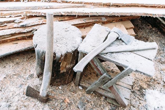 Рабочее место рубки дров с крупным планом топоров. оставленные на улице инструменты зимой. холодные, ранние заморозки, иней концепция