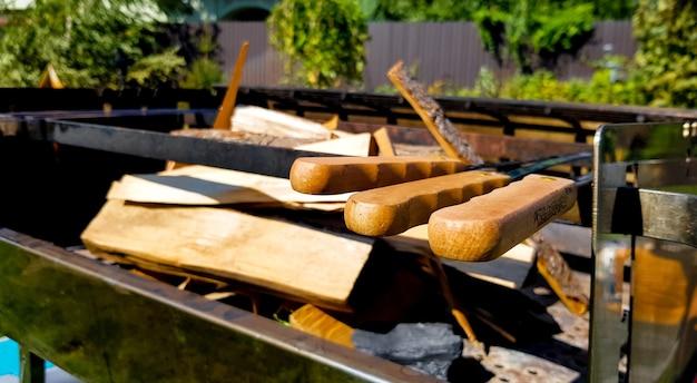 家の裏庭、バーベキューエリアにある大きな固定バーベキューの薪。グリルで肉や野菜を調理するための準備。緑の芝生で家族と一緒に夏のピクニック
