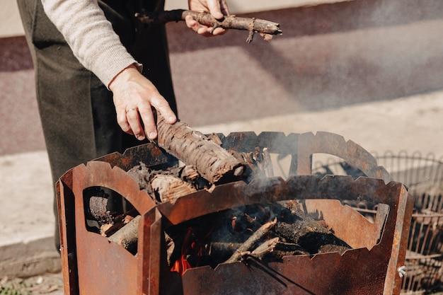 그릴에 장작. 남자는 고기를 굽고 모닥불을 발사합니다.