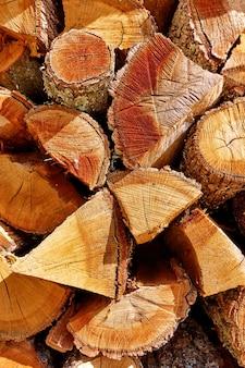 Дрова - стопка рубленых деревянных бревен крупным планом, деревянный текстурированный фон