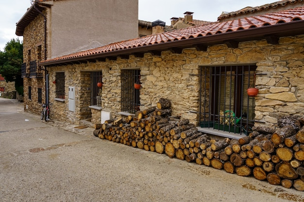 Firewood stacked on the facade of an old house made of stone and bicycle parked at the entrance. madrid.