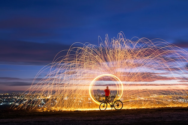 Firework showers of hot glowing sparks from spinning steel wool in night city.