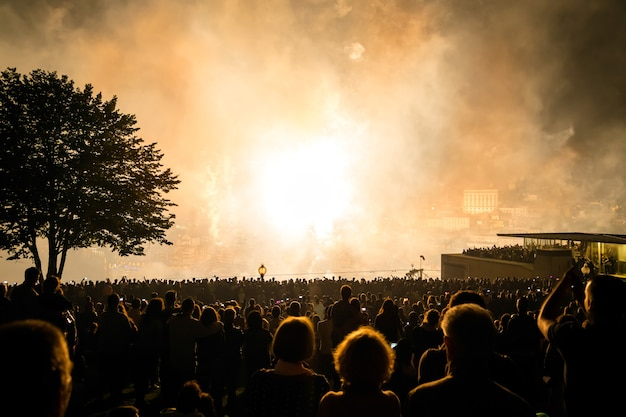 밤에 사람들 위의 축제에서 폭파하는 불꽃 놀이.