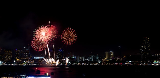 Fireworks explored over cityscape at night in sea port