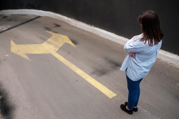 Девушка стоит возле двух стрелок, напечатанных на гранж-дороге, принимая решение