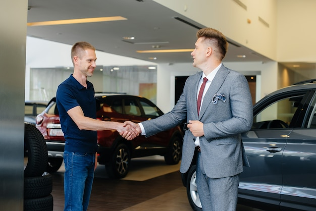 A firm handshake after buying a new car at a young family car dealership. cars sale.
