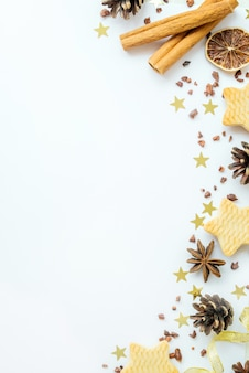 Firs, cookies, cinnamon and golden ribbons on white background. frame reeting new year card. christmas holiday concept. copy space, flat lay