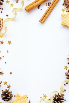 Firs, cookies, cinnamon and golden ribbons on white background. greeting new year card. christmas holiday concept. copy space, flat lay