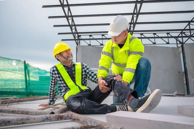 建設現場での緊急事故の応急処置。建設現場の高所からの転倒で建設作業員が負傷した。エンジニアは応急処置を支援し、安全チームは従業員の事故を支援します。