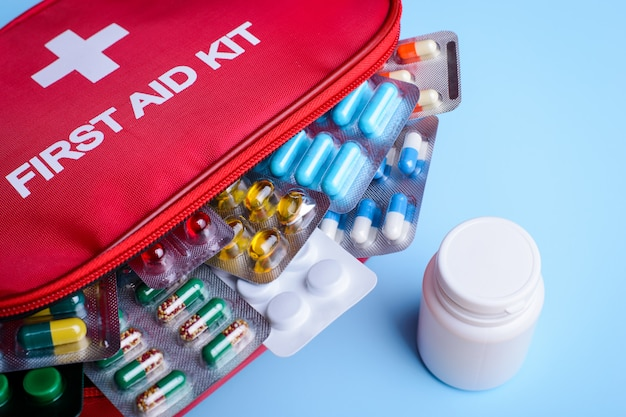 First aid kit full of different pills capsules medicine on light blue