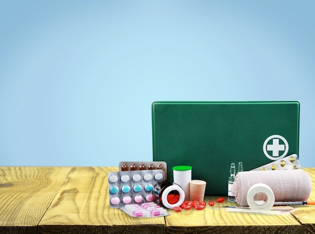 First aid kit and medicine on background
