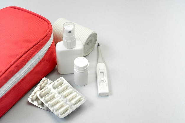 First aid kit red bag with medical equipment and medications for emergency treatment on gray background. copy space.