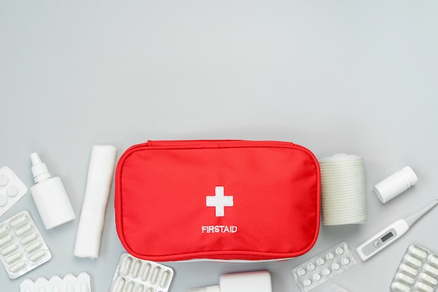 First aid kit red bag with medical equipment and medications for emergency treatment. top view flat lay on gray background. copy space.