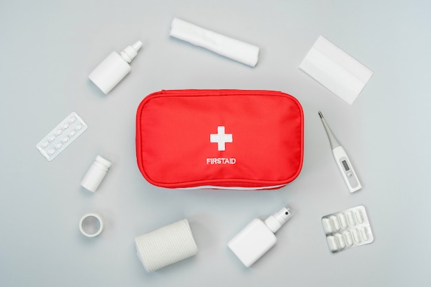 First aid kit red bag with medical equipment and medications for emergency treatment. top view flat lay on gray background.