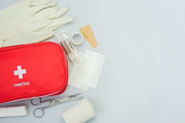 First aid kit red bag with medical equipment and medications for trauma and injuries treatment. top view flat lay on gray background. copy space.