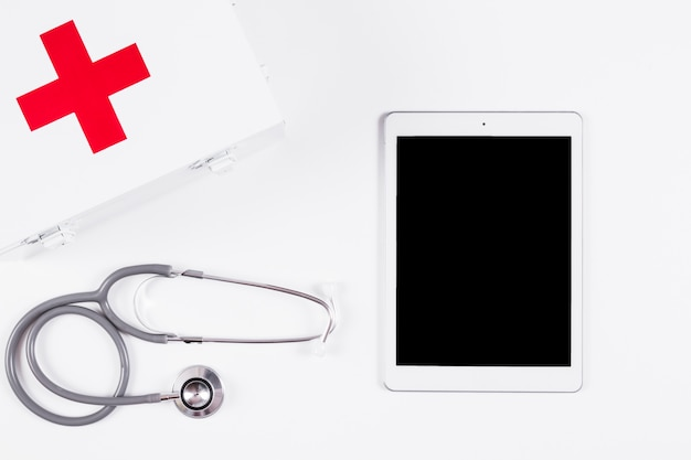 First aid kit; stethoscope and digital tablet on white background