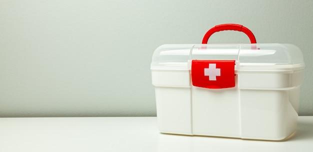 구급 상자. 회색 배경에 십자가와 빨간색 걸쇠가 있는 흰색 상자.