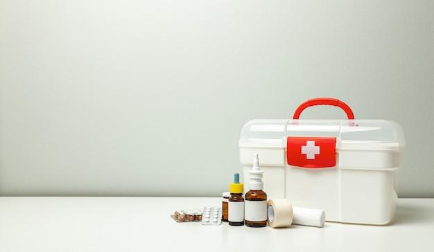 응급 처치 키트 십자가와 빨간색 패스너가 있는 흰색 상자, 약병이 있는 알약