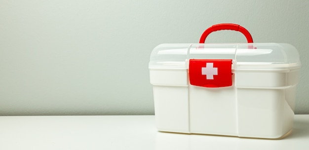 First aid kit. white box with a cross and a red clasp on a gray background.