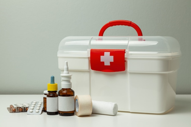 First aid kit white box with a cross and a red fastener and pills with medicine bottles