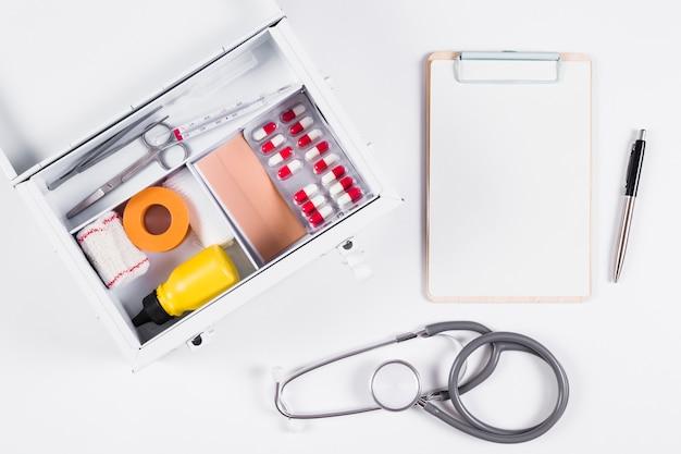 Аптечка первой помощи с буфером обмена; стетоскоп и ручка на белом фоне
