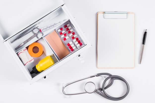 First aid kit with clipboard; stethoscope and pen on white background