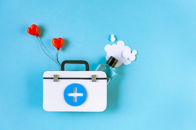 First aid kit with hand sanitizer on blue background
