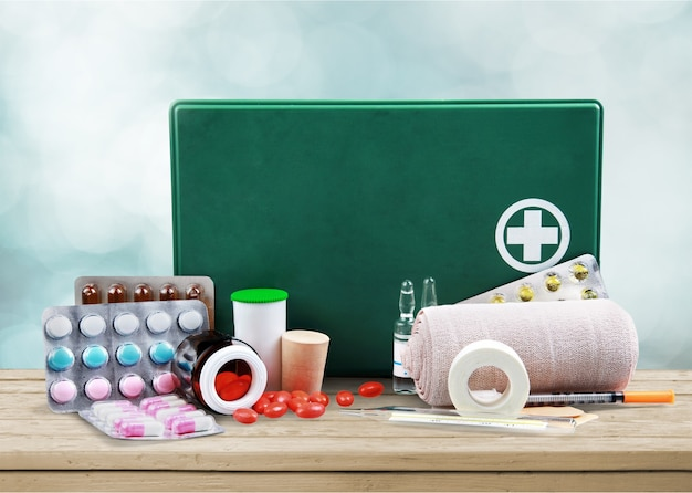 First aid kit  with medical supplies on light background
